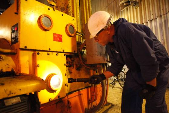 Employee of Israeli Electric Corporation examines the flow of coal into grinding mill.